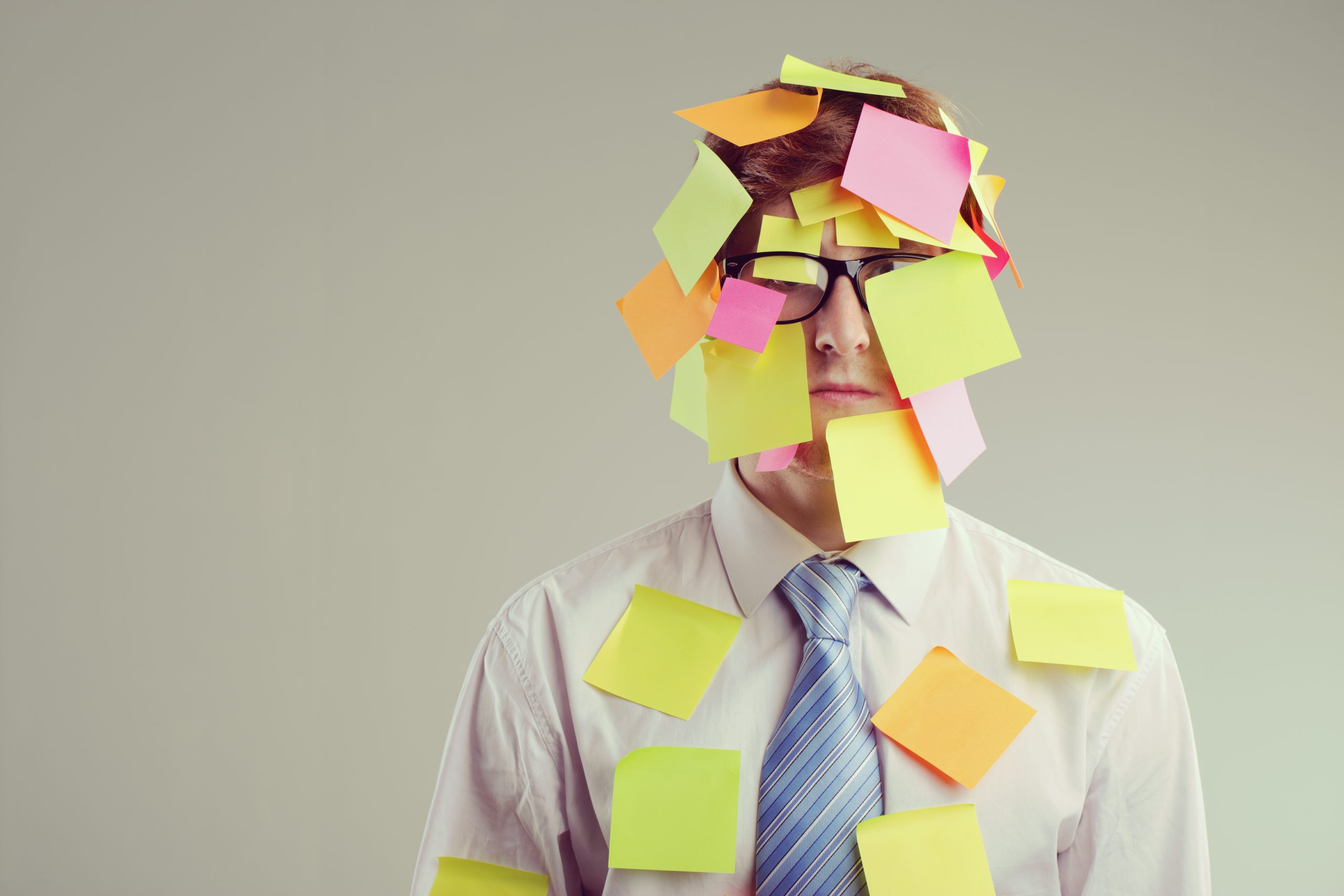 Office worker with post-its all over his face